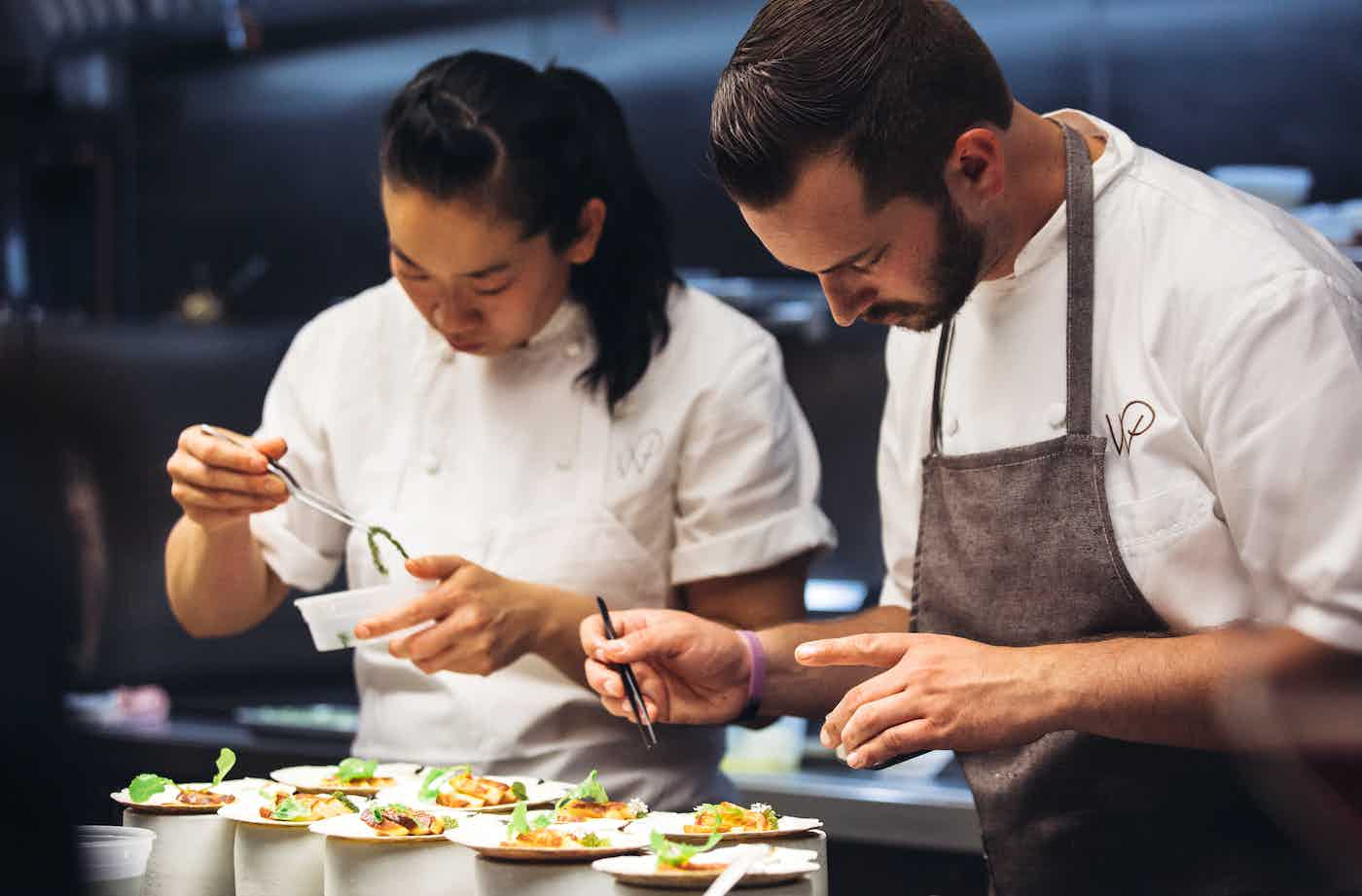 Two chefs plating dishes